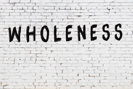 White brick wall with inscription wholeness handwritten with black paint