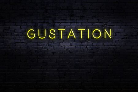 Neon sign with inscription gustation against brick wall. Night view