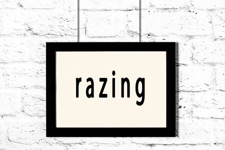 Black wooden frame with inscription razing hanging on white brick wall