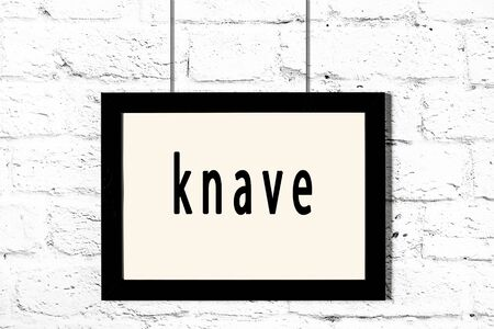 Black wooden frame with inscription knave hanging on white brick wall