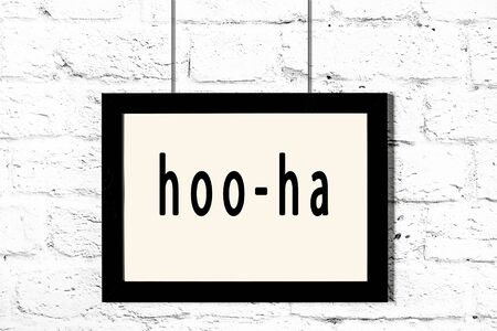 Black wooden frame with inscription hoo-ha hanging on white brick wall 写真素材