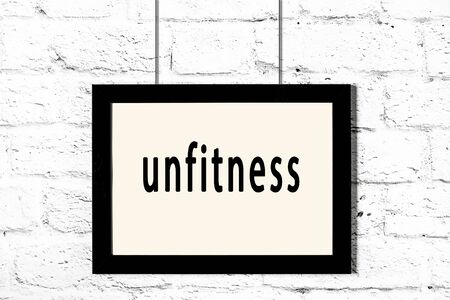 Black wooden frame with inscription unfitness hanging on white brick wall
