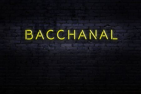 Neon sign with inscription bacchanal against brick wall. Night view