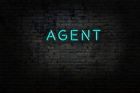 Night view of neon sign on brick wall with inscription agent Фото со стока