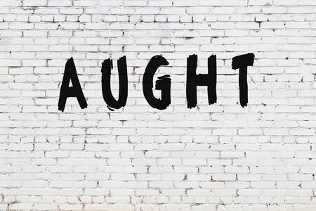 Word aught written with black paint on white brick wall. Stok Fotoğraf