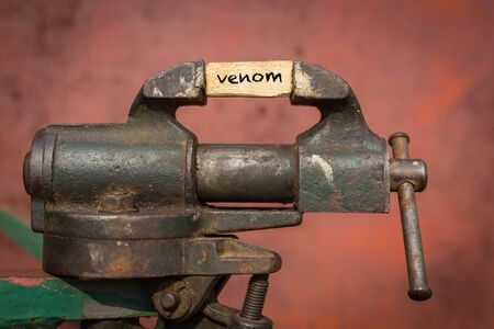 Concept of dealing with problem. Vice grip tool squeezing a plank with the word venom