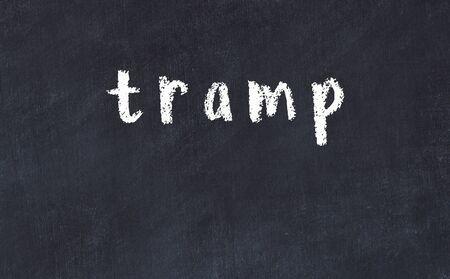 Chalk handwritten inscription tramp on black desk 스톡 콘텐츠
