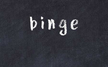 Chalk handwritten inscription binge on black desk