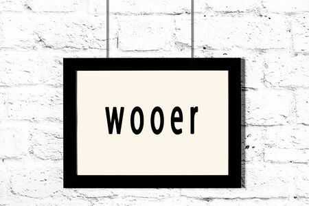 Black wooden frame with inscription wooer hanging on white brick wall