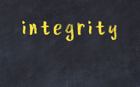 Chalk handwritten inscription integrity on black desk 스톡 콘텐츠