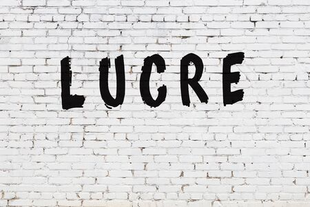 Word lucre written with black paint on white brick wall.