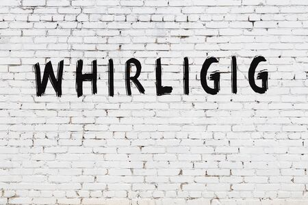 Word whirligig written with black paint on white brick wall. Reklamní fotografie
