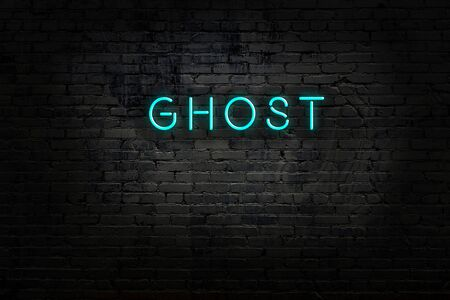 Night view of neon sign on brick wall with inscription ghost