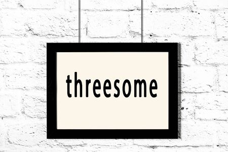 Black wooden frame with inscription threesome hanging on white brick wall Stockfoto