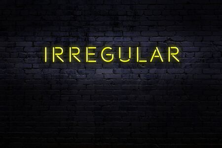 Neon sign with inscription irregular against brick wall. Night view