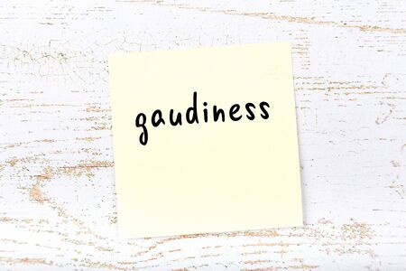 Concept of reminder about gaudiness. Yellow sticky sheet of paper on wooden wall with inscription