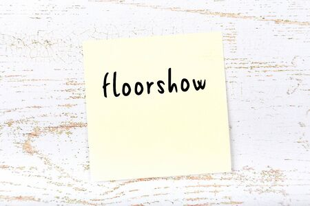 Concept of reminder about floorshow. Yellow sticky sheet of paper on wooden wall with inscription