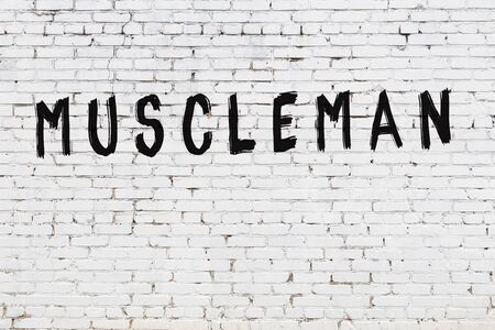 Word muscleman written with black paint on white brick wall. Standard-Bild