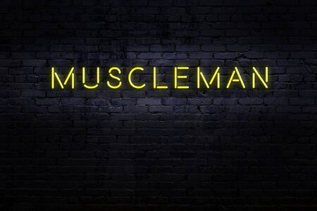 Neon sign with inscription muscleman against brick wall. Night view Standard-Bild