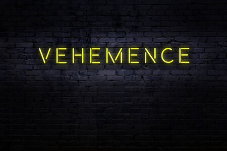Neon sign with inscription vehemence against brick wall. Night view