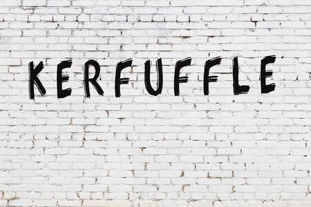 Word kerfuffle written with black paint on white brick wall.