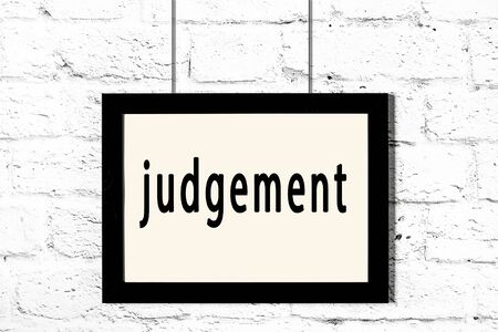 Black wooden frame with inscription judgement hanging on white brick wall Imagens