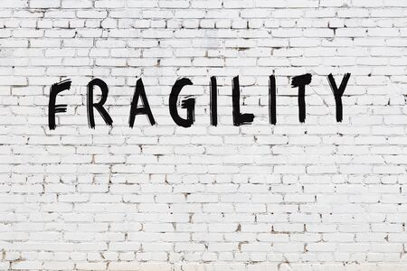 White brick wall with inscription fragility handwritten with black paint