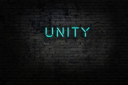 Neon sign with inscription unity against brick wall. Night view
