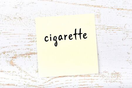 Concept of reminder about cigarette. Yellow sticky sheet of paper on wooden wall with inscription Stok Fotoğraf