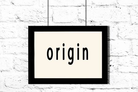 Black wooden frame with inscription origin hanging on white brick wall