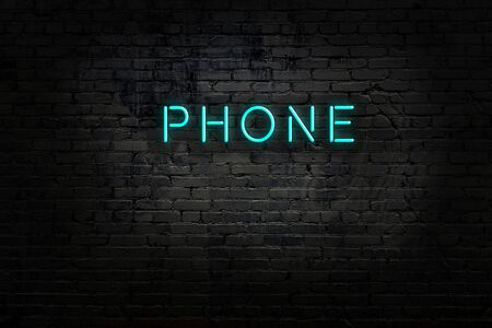 Night view of neon sign on brick wall with inscription phone