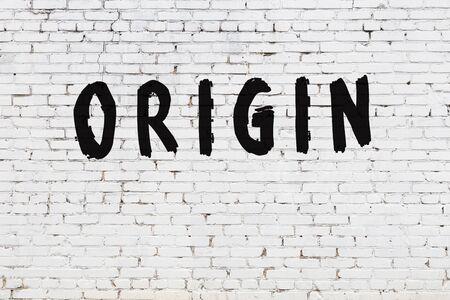 Word origin written with black paint on white brick wall.