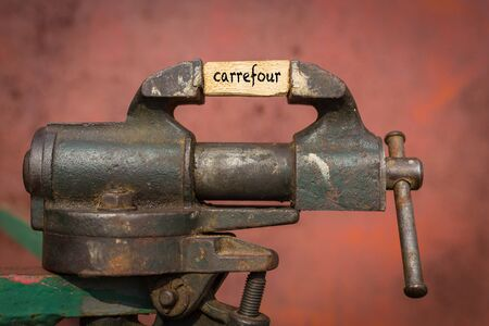 Concept of dealing with problem. Vice grip tool squeezing a plank with the word carrefour