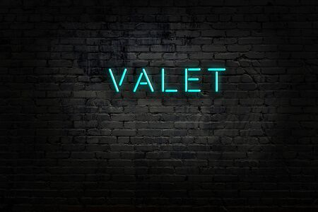 Neon sign with inscription valet against brick wall. Night view