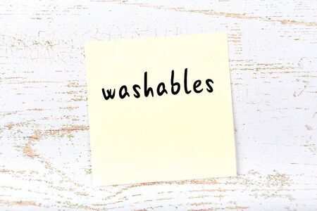 Concept of reminder about washables. Yellow sticky sheet of paper on wooden wall with inscription