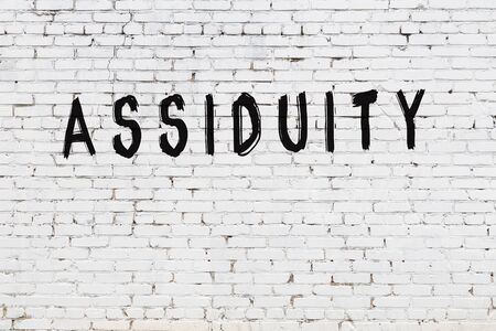 Word assiduity written with black paint on white brick wall.
