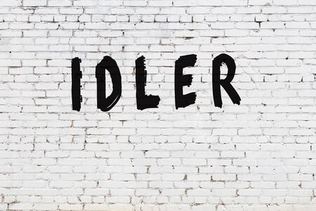 Word idler written with black paint on white brick wall.