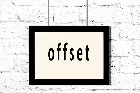 Black wooden frame with inscription offset hanging on white brick wall Banque d'images