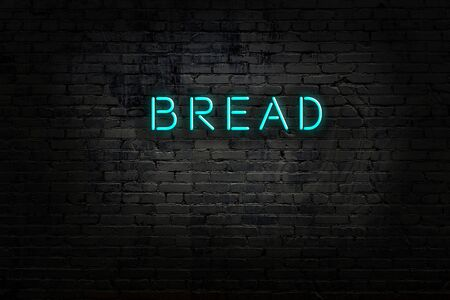 Neon sign with inscription bread against brick wall. Night view