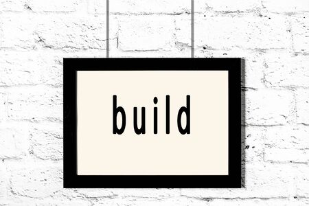 Black wooden frame with inscription build hanging on white brick wall