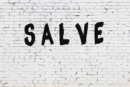 Word salve written with black paint on white brick wall.