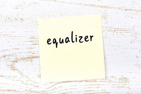 Concept of reminder about equalizer. Yellow sticky sheet of paper on wooden wall with inscription
