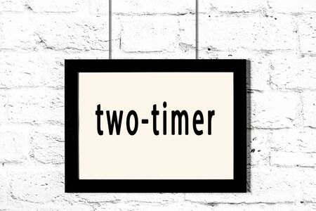 Black wooden frame with inscription two-timer hanging on white brick wall Stock Photo