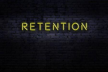 Neon sign on brick wall at night. Inscription retention