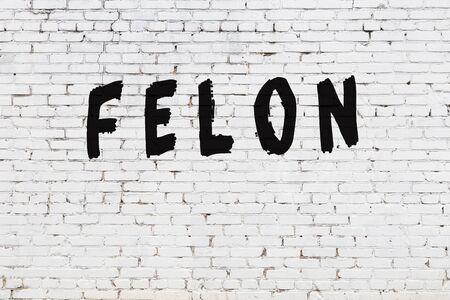 Word felon written with black paint on white brick wall. Stock Photo