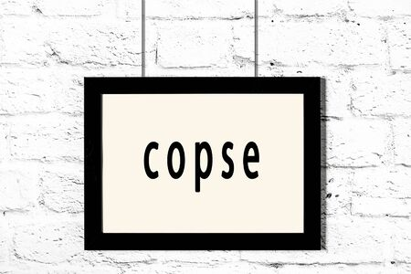 Black wooden frame with inscription copse hanging on white brick wall