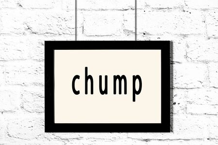 Black wooden frame with inscription chump hanging on white brick wall
