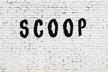 Word scoop written with black paint on white brick wall.
