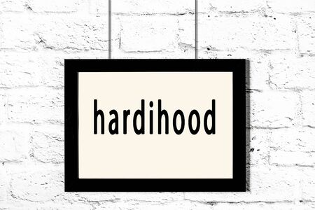 Black wooden frame with inscription hardihood hanging on white brick wall