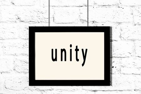 Black wooden frame with inscription unity hanging on white brick wall